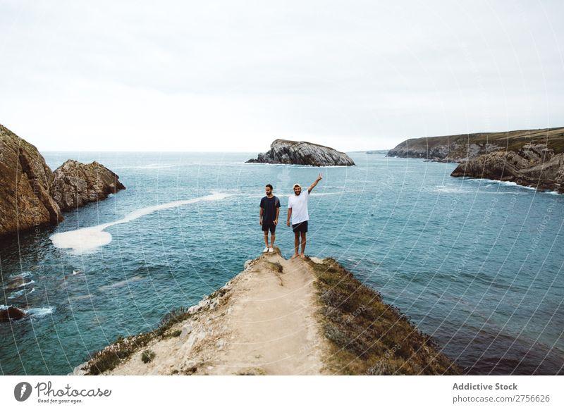 Männer, die auf einer Klippe am Meer stehen. Mann Tourist Felsen heiter Freundschaft Zusammensein Ferien & Urlaub & Reisen Tourismus Natur Landschaft Küste