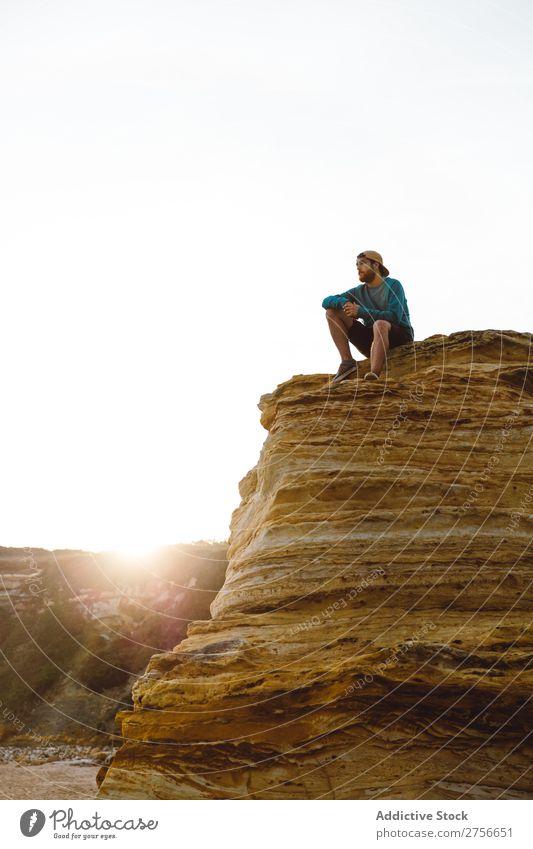 Mann sitzt auf einer Klippe. Tourist Felsen Ferien & Urlaub & Reisen Tourismus Natur Landschaft sitzen ruhen Sonne Freiheit Stein natürlich Lifestyle schön