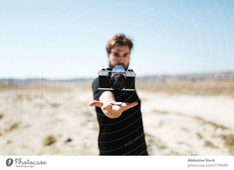 Mann mit Kamera über der Hand Fotokamera Illusion Trick Wüste Ferien & Urlaub & Reisen Lifestyle