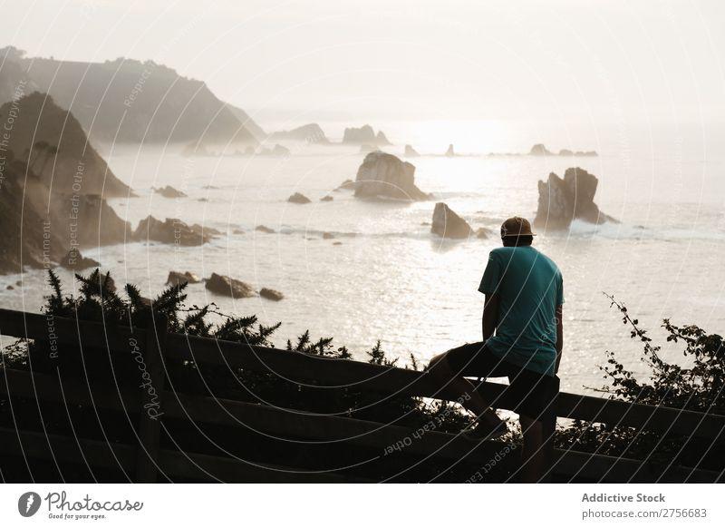 Mann sitzt auf einem Zaun an einer Felsküste. Klippe Meer Felsen Ferien & Urlaub & Reisen Tourismus Natur Landschaft Küste Wasser Sonne Freiheit Stein natürlich