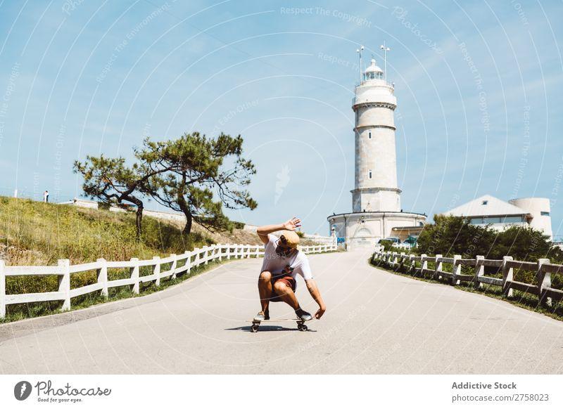 Mann Skateboarding am Leuchtfeuer Skateboarderin Reiten Asphalt Leuchtturm Seeküste Sport Lifestyle Schlittschuhlaufen Schlittschuhe extrem Sonnenstrahlen
