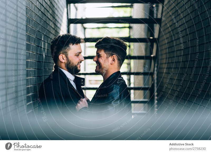 Schwules Paar, das sich an der Treppe umarmt. Umarmen Homosexualität umarmend Feuer paarweise stehen Wand Backstein Mann Liebe 2 Zusammensein Lifestyle