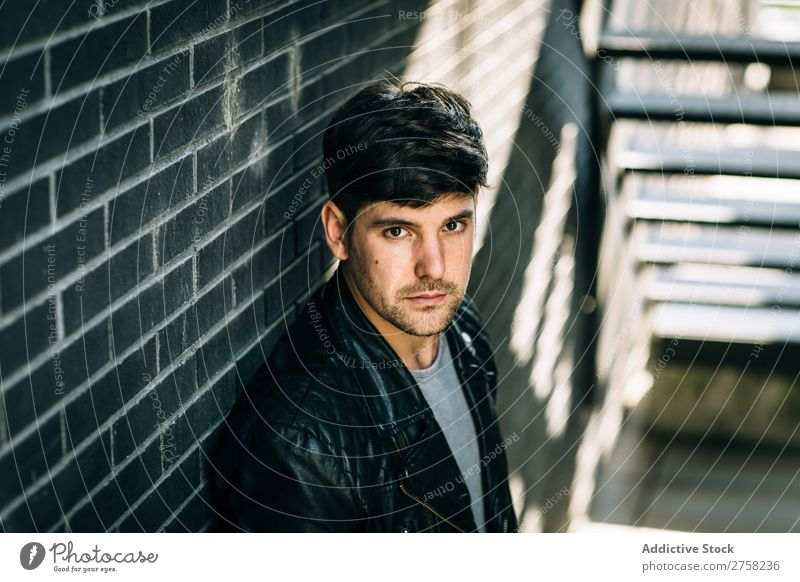 Junger, nachdenklicher Mann in der Nähe der Feuertreppe stylisch besinnlich in die Kamera schauen Sitzen Treppe selbstbewusst jung cool Person Porträt modern