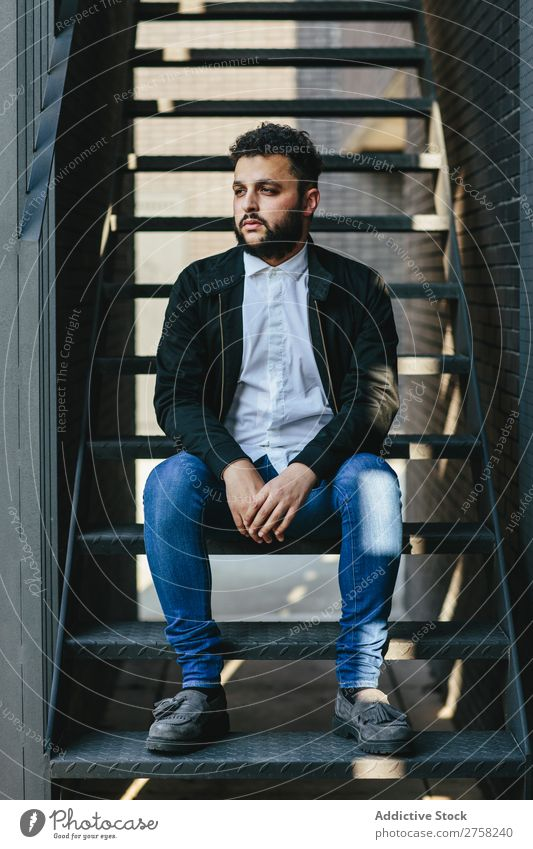 Nachdenklicher Mann sitzt auf der Treppe stylisch besinnlich nachdenklich in die Kamera schauen Sitzen selbstbewusst jung cool Person Porträt modern Model