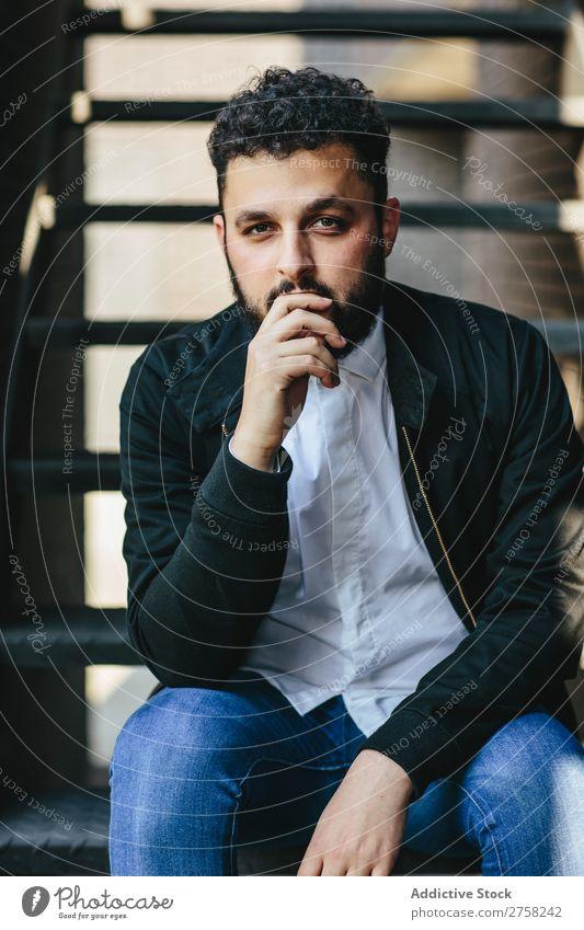 Nachdenklicher Mann, der auf der Treppe sitzt. Stil besinnlich Fürsorge Blick in die Kamera sitzen selbstbewußt Jugendliche Coolness Mensch Porträt modern Model