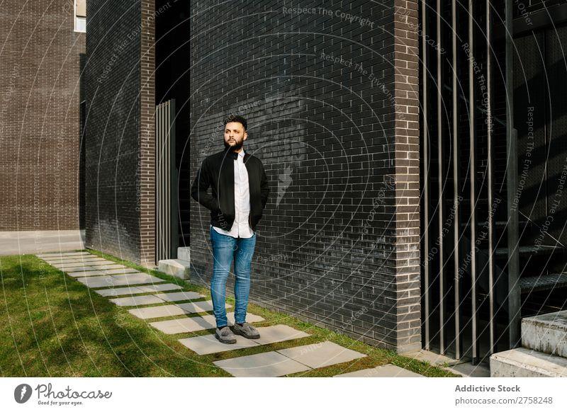 Modischer junger Mann auf der Straße Wegsehen nachdenklich besinnlich stylisch Baustein Wand Stehen selbstbewusst cool Person Porträt modern Model modisch