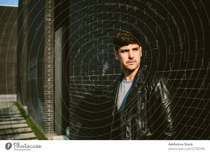 Junger, gut aussehender Mann über einer dunklen Ziegelmauer ernst Sonnenbrille selbstbewusst jung cool Person Porträt modern Model modisch männlich lässig