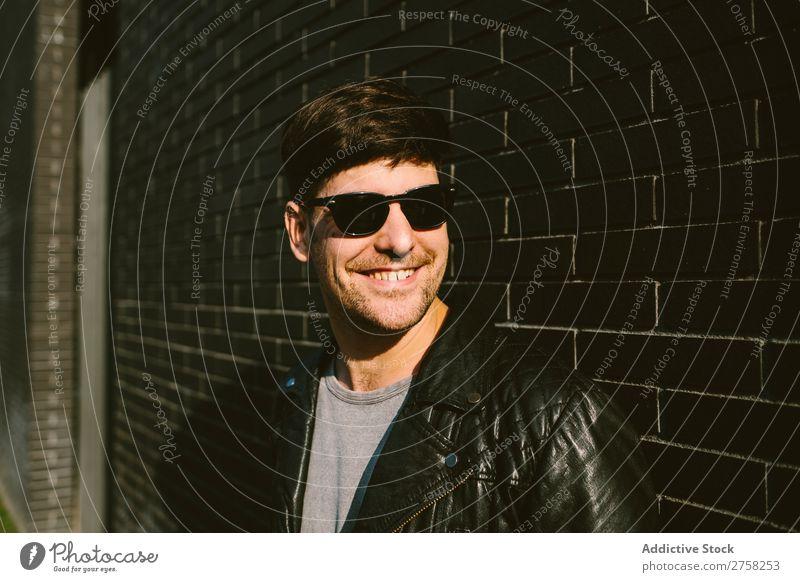 Fröhlicher Mann mit Sonnenbrille heiter Lächeln Glück selbstbewusst jung cool Person Porträt modern Model modisch männlich ernst lässig gutaussehend Typ