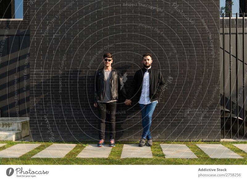 Alternatives Paar an der Ziegelwand stehen Wand Backstein Händchenhalten Blick in die Kamera Körperhaltung Homosexualität paarweise Mann Liebe 2 Zusammensein