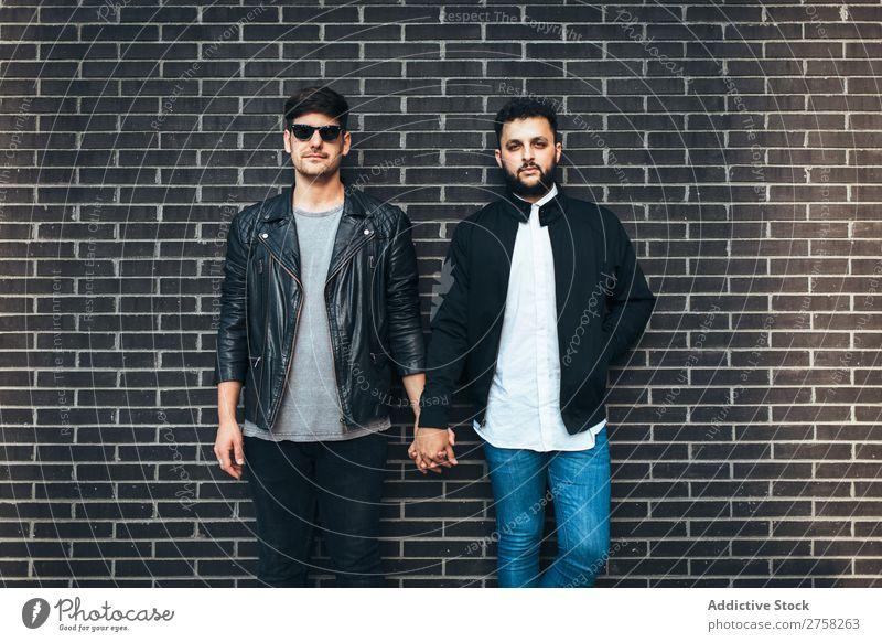 Schwules Paar, das Händchen hält. stehen Wand Backstein Händchenhalten Blick in die Kamera Körperhaltung Homosexualität paarweise Mann Liebe 2 Zusammensein