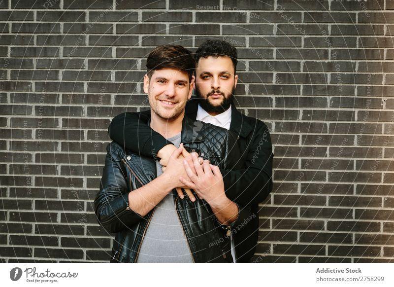 Schwules Paar, das sich in der Nähe der Ziegelmauer umarmt. Homosexualität Umarmen Blick in die Kamera Glück stehen Wand Backstein Körperhaltung paarweise Mann