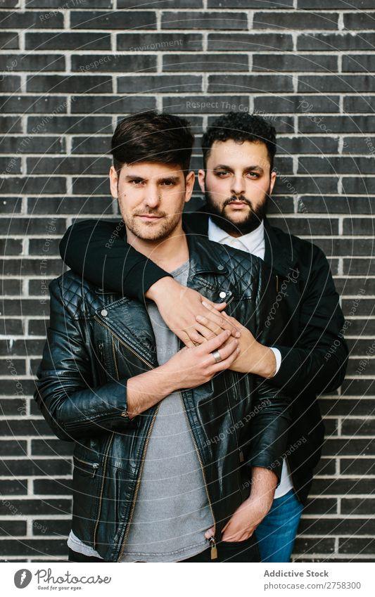 Schwules Paar umarmt sich in der Nähe einer Ziegelmauer schwul Umarmen umarmend in die Kamera schauen Glück Stehen Wand Baustein posierend Homosexualität