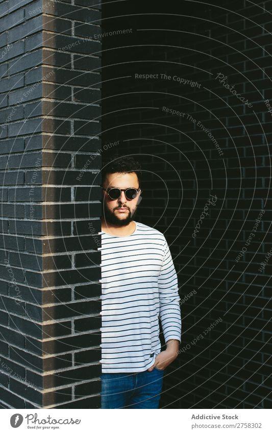 Selbstbewusster Mann mit stylischer Sonnenbrille Blick in die Kamera Fürsorge besinnlich Stil Backstein Wand stehen selbstbewußt Jugendliche Coolness Mensch