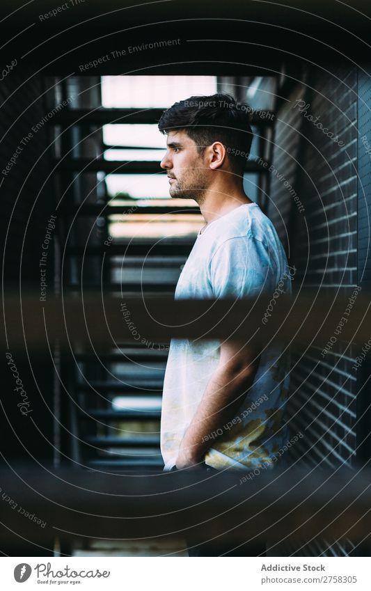Mann, der an der Ziegelmauer posiert. Wand Körperhaltung Backstein Treppe Profil selbstbewußt Jugendliche Coolness Mensch Porträt modern Model modisch ernst