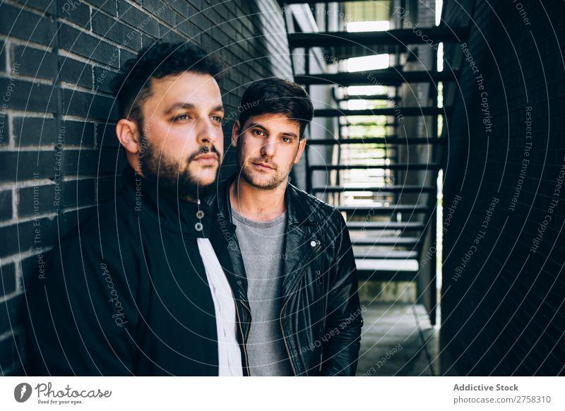 Alternatives Paar in der Nähe der Treppe Homosexualität Feuer paarweise stehen Wand Backstein Mann Liebe 2 Zusammensein Lifestyle Partnerschaft lässig Freund