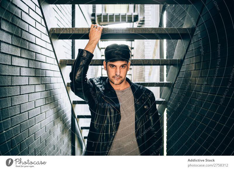 Cooler Mann, der eine Stufe hält. Schritt selbstbewußt Jugendliche Treppe Jacke Leder Coolness Mensch Porträt modern Model modisch ernst heiter Lächeln lässig