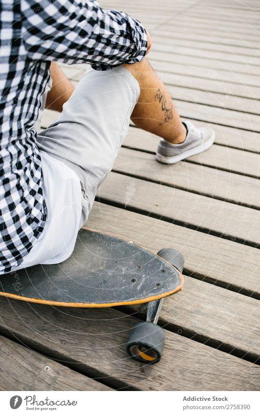Tätowierter Mann auf Skateboard sitzend Skateboarderin Schlittschuhe Stadt Sport Skateboarding Jugendliche Holzplatte Schlittschuhlaufen Mensch Lifestyle Typ
