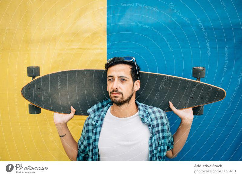 Bartiger Mann hält Skateboard. Jugendliche Hintergrundbild Sport Skateboarderin Skateboarding Schlittschuhe Lifestyle Stadt Holzplatte modern Sommer extrem