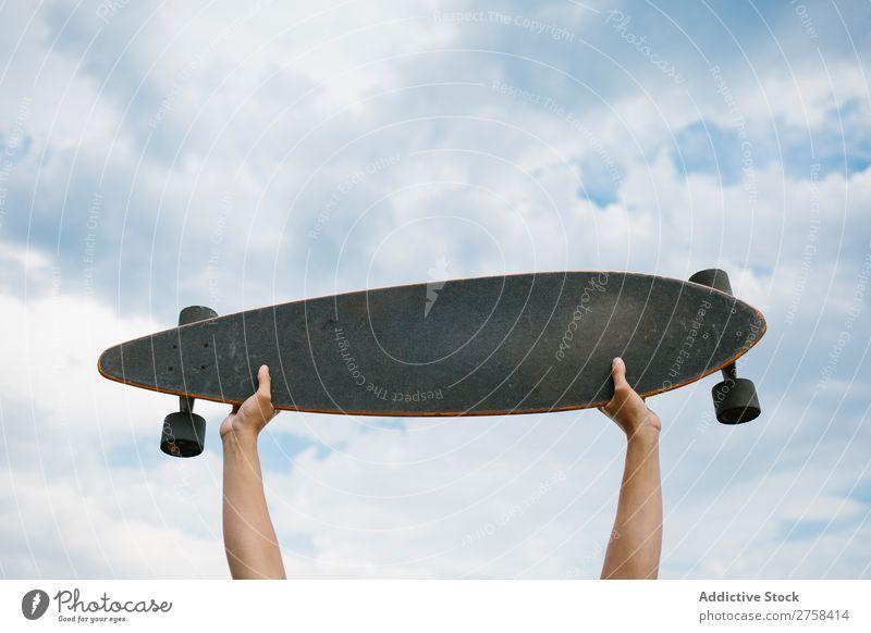 Hände halten das Skateboard. Hand Halt Himmel Wolken in der Höhe Feldfrüchte Freizeit & Hobby Youngster Sport Schlittschuhe Skateboarding Skateboarderin