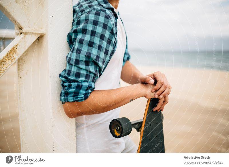 Mann steht mit Skateboard am Ufer. Küste Strand Freizeit & Hobby Sommer mehrfarbig Youngster Aktion Jugendliche Sport Schlittschuhe Skateboarding Skateboarderin