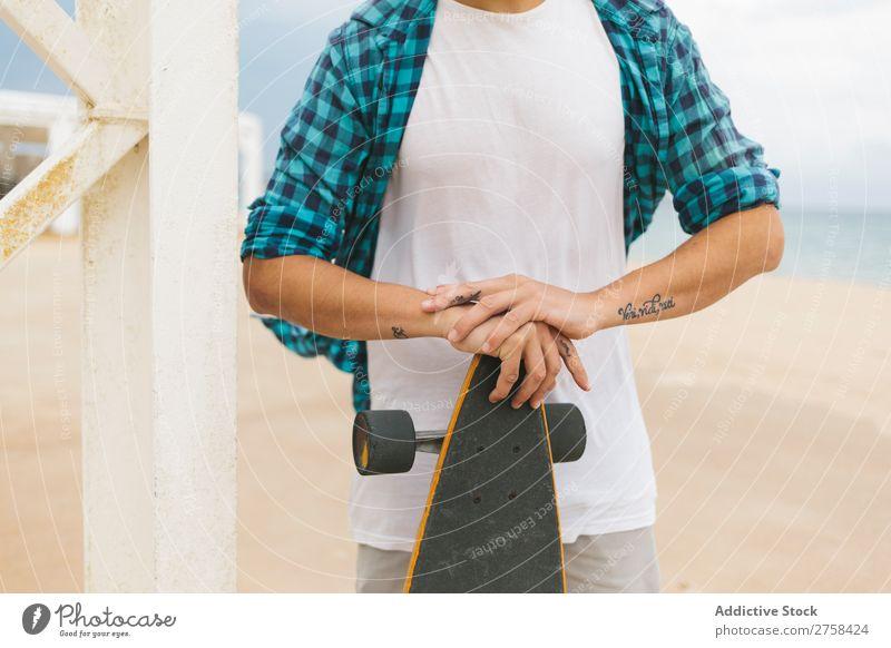 Mann in Sommerkleidung hält Skateboard am Sandstrand. Küste Strand Freizeit & Hobby mehrfarbig Youngster Aktion Jugendliche Sport Schlittschuhe Skateboarding
