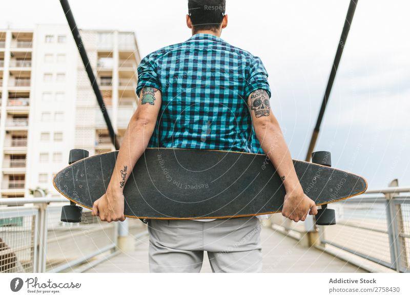 Mann mit Tattoos, der Skateboard an Land hält. Rückansicht. Küste Strand Freizeit & Hobby Sommer mehrfarbig Youngster Aktion Jugendliche Sport Schlittschuhe