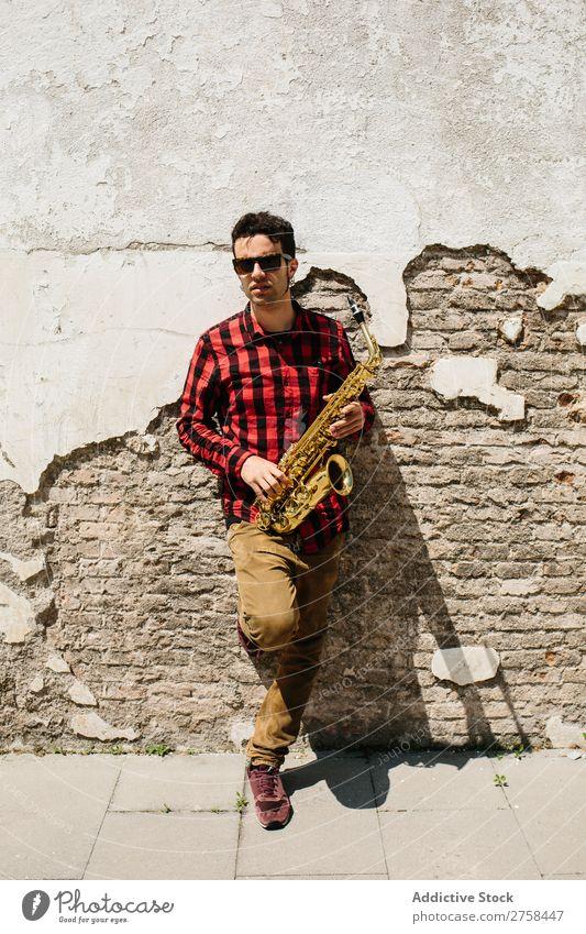 Cooler Musiker mit Saxophon Mann Sonnenbrille selbstbewußt Coolness Wand Jugendliche Jazz Instrument Musical Leistung Saxophonspieler Mensch Spieler Artist
