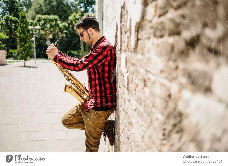 Lächelnder Jazzmann mit Saxophon Musiker Mann Sonnenbrille selbstbewußt Coolness heiter Wand Jugendliche Instrument Musical Leistung Saxophonspieler Mensch