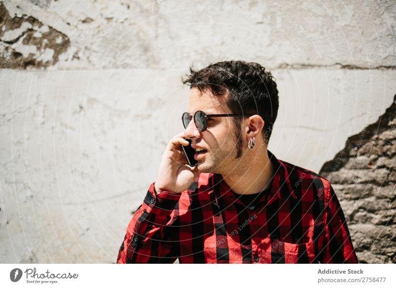 Stilvolles Männergespräch Telefon Mann PDA sprechen Wand Sonnenstrahlen Mobile gutaussehend Coolness Porträt Lifestyle Mitteilung lässig Jugendliche