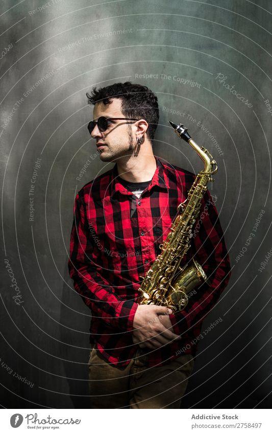 Seitenansicht des jungen Saxophonisten im Stehen mit lehnendem Instrument Musiker Mann Jugendliche Jazz Musical Leistung Saxophonspieler Mensch Spieler Artist