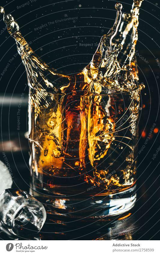 Spritzer von Glas Whiskey Alkohol Getränk Bourbon braun Cocktail kalt Coolness Kristalle Würfel dunkel trinken Tropfen elegant Glaswaren Eis liquide Reichtum