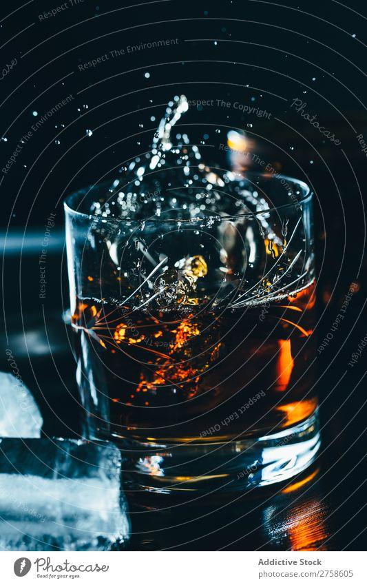 Ein Glas spritzender Whiskey Alkohol Getränk Bourbon braun Cocktail kalt Coolness Kristalle Würfel dunkel trinken Tropfen elegant Vogelperspektive Glaswaren Eis