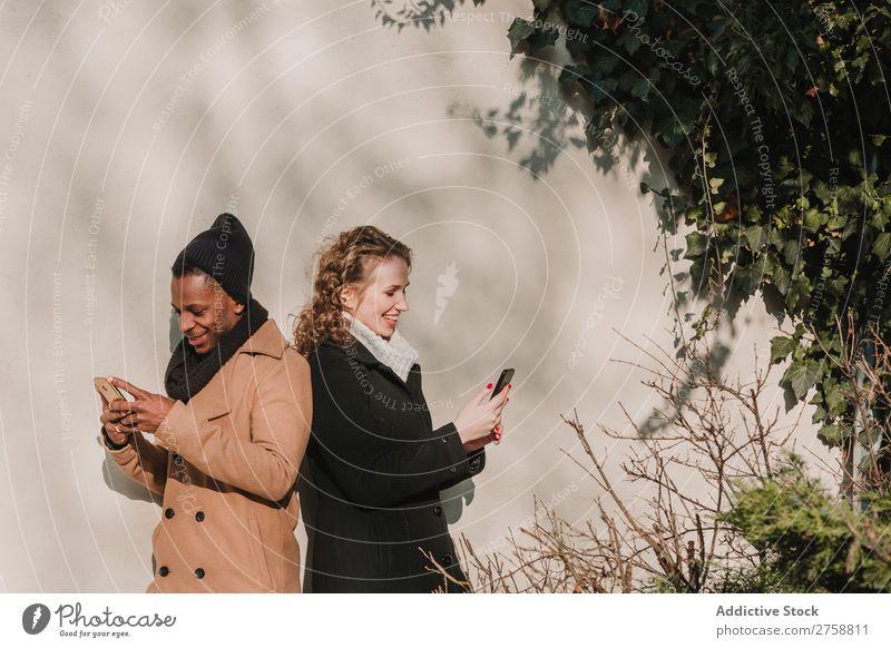 Paar in warmer Kleidung mit Smartphones Stil Straße PDA stehen lässig schön Person gemischter Abstammung