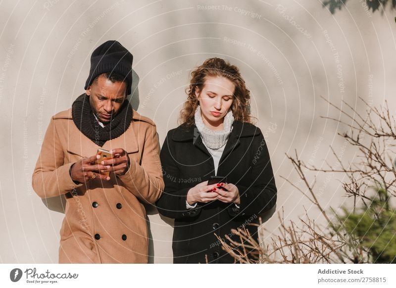 Paar in warmer Kleidung mit Smartphones multiethnisch Stil Straße warme Kleidung PDA benutzend stehen lässig schön Person gemischter Abstammung schwarz
