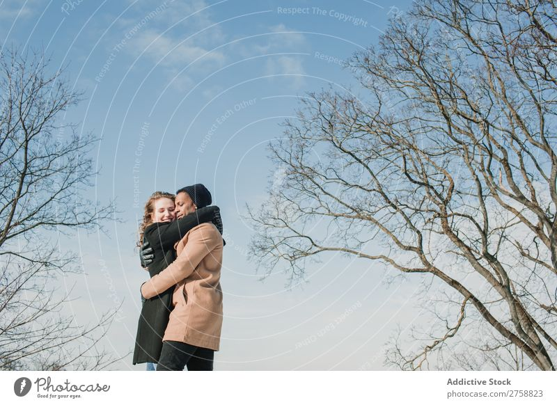 Ein Paar, das sich an nackten Bäumen umarmt. multiethnisch Stil Straße warme Kleidung Baum laublos lässig umarmend schön Person gemischter Abstammung schwarz