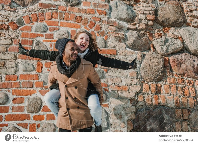 Paar hat Spaß an der Ziegelwand multiethnisch Stil Straße warme Kleidung lässig Backstein Wand tragen auf der Rückseite Stein Huckepack schön