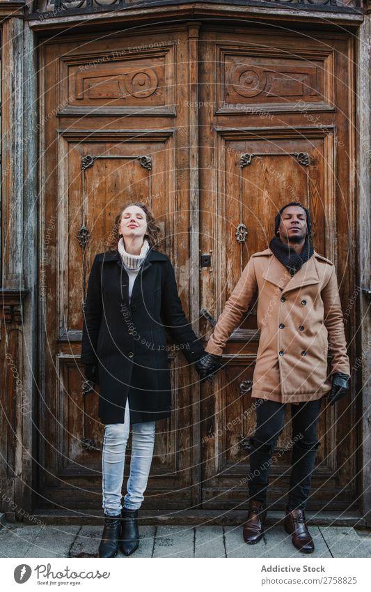 Ein Paar hält sich an der Vintage-Tür an den Händen. multiethnisch Stil Straße warme Kleidung Augen geschlossen Händchenhalten Holz schäbig lässig schön