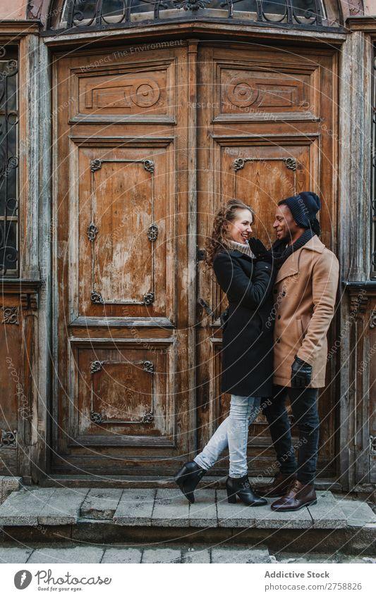 Paar an der Vintage-Tür umarmt multiethnisch Stil Straße warme Kleidung Holz schäbig alt lässig schön Person gemischter Abstammung schwarz Jugendliche
