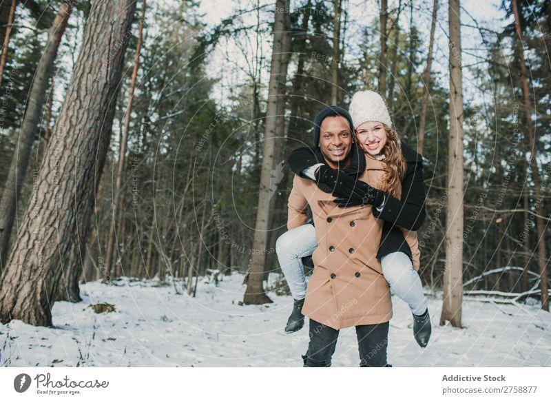 Ein Paar mit Spaß im Winterwald multiethnisch Stil warme Kleidung lässig Natur Wald Schnee Huckepack schön Person gemischter Abstammung schwarz Jugendliche