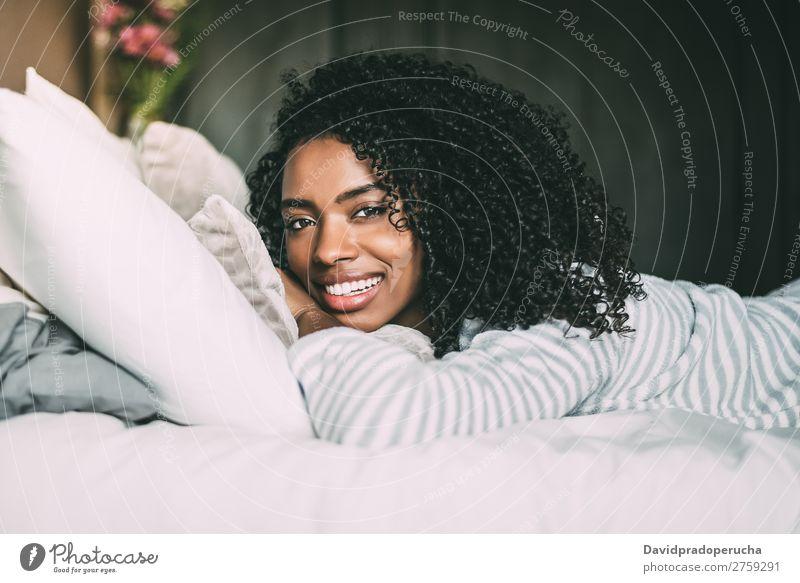 Nahaufnahme einer hübschen schwarzen Frau mit lockigem Haar, die lächelt und auf dem Bett liegt und auf die Kamera schaut. Porträt lügen Lächeln