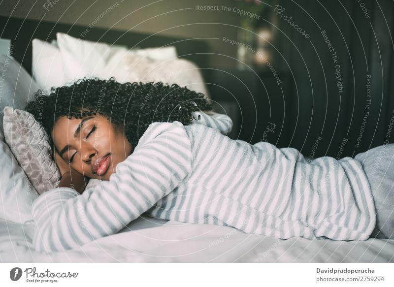 Nahaufnahme einer hübschen schwarzen Frau mit lockigem Haar, die im Bett schläft geschlossene Augen schwarze Frau schlafen Porträt lügen Lächeln Afrikanisch