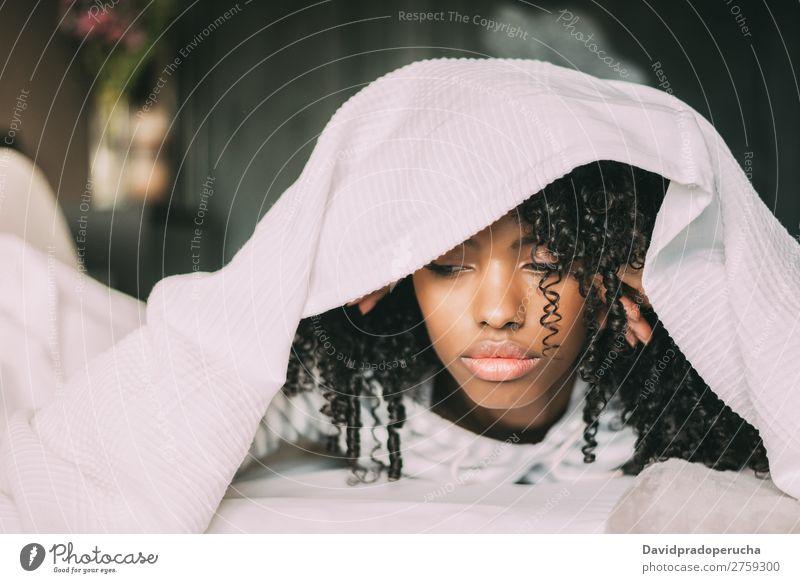 Wunderschöne, ernsthaft nachdenkliche und traurige schwarze Frau, die ihren Kopf mit Laken im Bett bedeckt. Traurigkeit Wut deckend