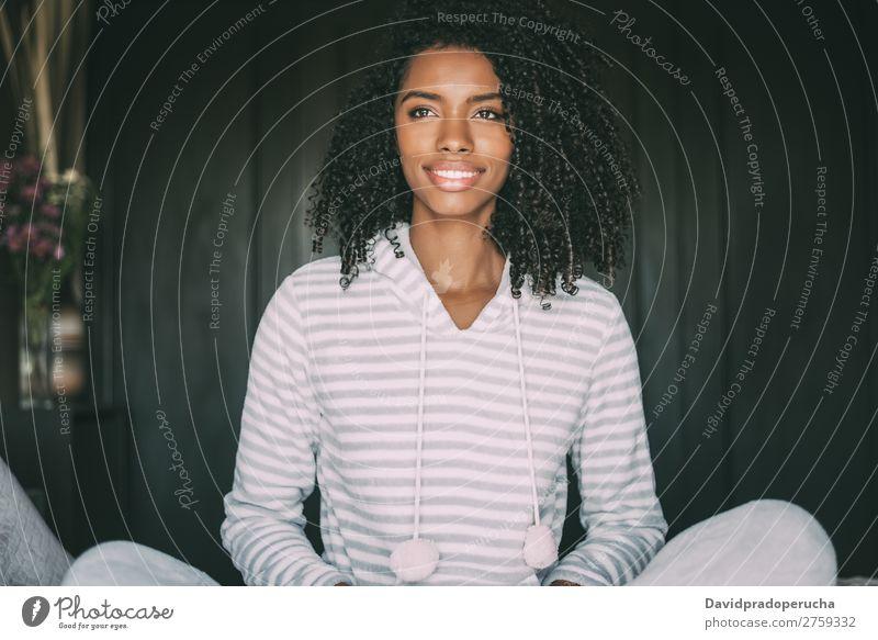 Nahaufnahme einer hübschen schwarzen Frau mit lockigem Haar, die lächelt und auf dem Bett liegt und wegblickt. schwarze Frau Porträt lügen Lächeln Wegsehen