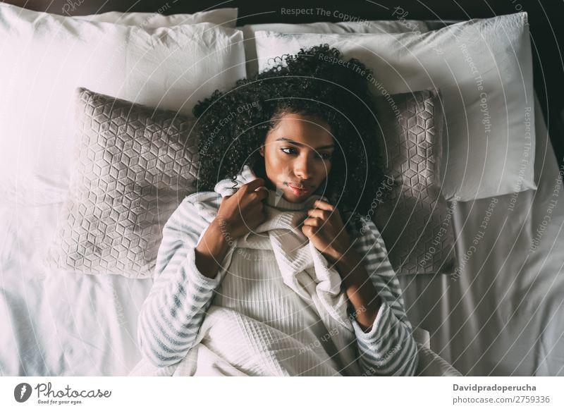 Schöne nachdenkliche schwarze Frau mit lockigem Haar, die auf dem Bett liegt und wegblickt. Fürsorge Afrikanisch schön Vogelperspektive