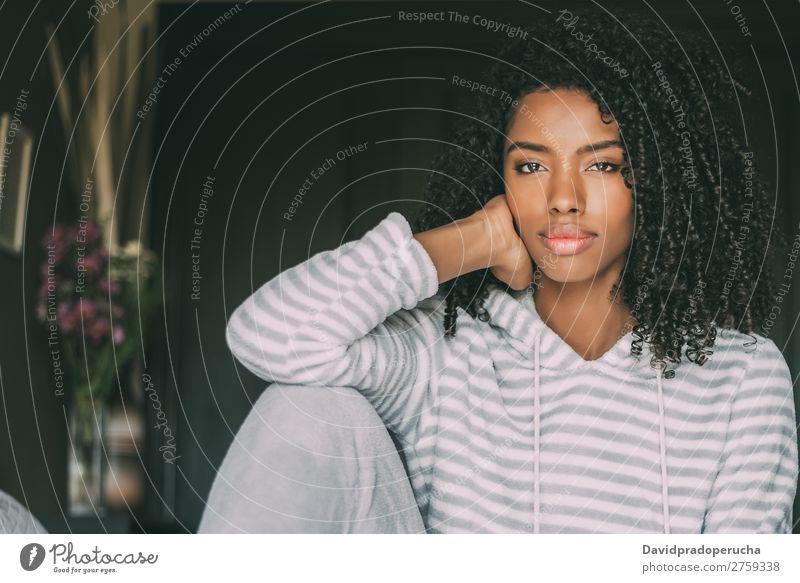 Schöne nachdenkliche schwarze Frau sitzt auf dem Bett und schaut auf die Kamera. Fürsorge Afrikanisch Feldfrüchte schön sitzen