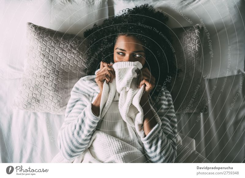 Hübsche schwarze Frau bedeckt ihren Mund mit dem Laken, das wegblickt. Bett Bettlaken deckend Afrikanisch Feldfrüchte hübsch schön Vogelperspektive Nahaufnahme
