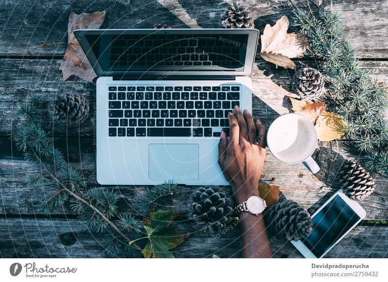 Computer auf einem Holztisch mit Kaffee und Kiefern im Freien Weihnachten & Advent Notebook Technik & Technologie Hand Arme beobachten Mobile