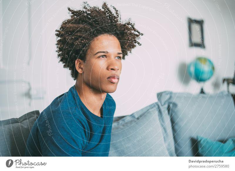 Porträt eines jungen nachdenklichen gemischtrassigen Mannes, der auf dem Sofa sitzt. schwarz Jugendliche Mensch Rennsport Amerikaner Afrikanisch