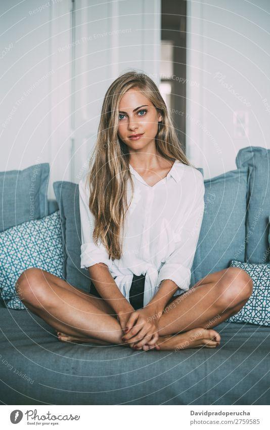 Porträt einer jungen nachdenklichen blonden Frau, die auf dem Sofa sitzt. sitzen Liege Raum Lächeln Jugendliche Fürsorge hübsch Nahaufnahme Leben heimwärts