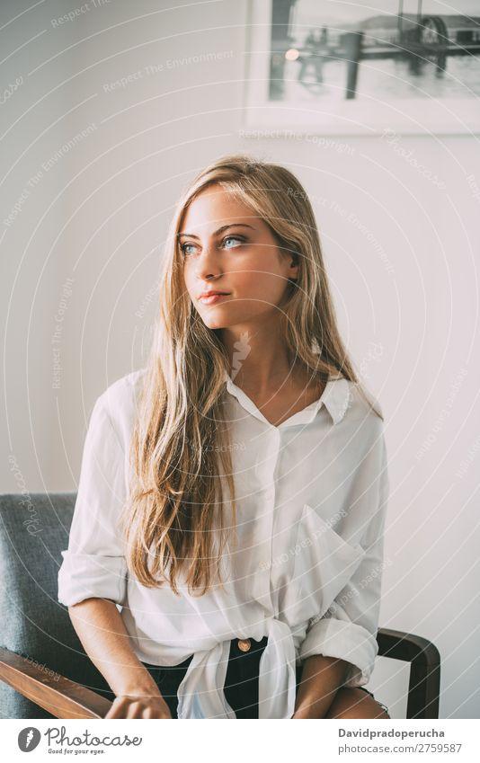 Porträt einer jungen nachdenklichen blonden Frau im Sitzen sitzen Raum Lächeln Jugendliche Fürsorge hübsch Nahaufnahme Leben heimwärts Glück schön Kaukasier